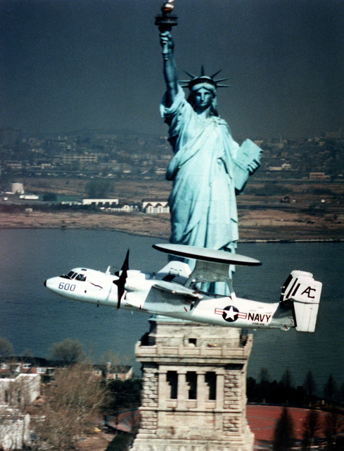 An Airborne Early Warning Squadron 126 (VAW-126) E-2 Hawkeye aircraft flies past the Statue of Liberty