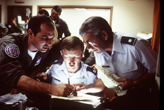 Captain Rick Vandam, left, CAPT. Vaugon Hanchett, center and Lieutenant Colonel Edward Coppin, members of the 152nd Tactical Reconnaissance Group, Air National Guard, select the best photographic image following a mission during Reconnaissance Air Meet '86