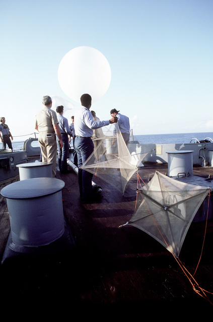 Crew members release a weather/wind velocity balloon prior to a remote-piloted vehicle launch aboard the battleship USS IOWA (BB-61)
