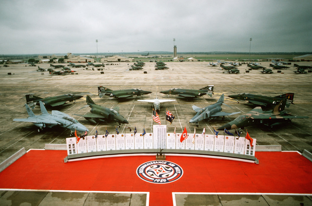 The five types of aircraft used in Reconnaissance Air Meet (RAM) '86 are arrayed behind the competition scoreboard on the flight line. The aircraft in the front row are, from left: a Navy F-14A Tomcat, an Air Force RF-4C Phantom II, a Navy Reserve RF-8G Crusader, a Marine Corps RF-48 Phantom and a Royal Australian Air Force RF-111C. In the back row are four Air Force RF-4C Phantom II aircraft