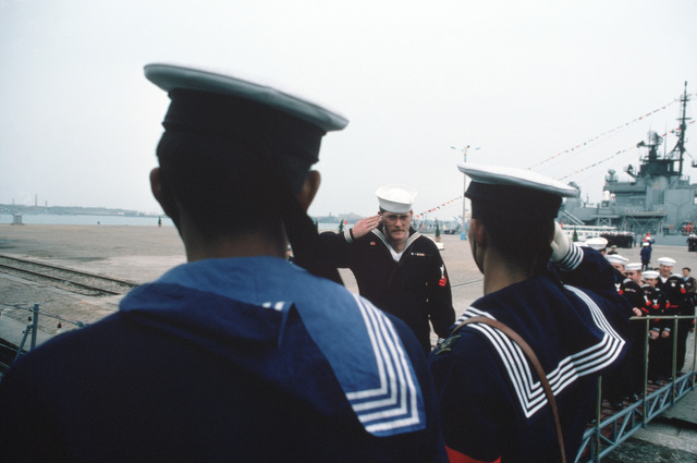 US Navy personnel salute and request permission to come aboard a Chinese ship during the first visit by US Navy (USN) ships to China in 40 years