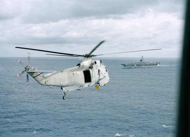 An air to air right rear view of a Helicopter Anti-submarine Squadron Nine (HS-9) SH-3H Sea King helicopter approaching the nuclear-powered aircraft carrier USS NIMITZ (CVN 68)