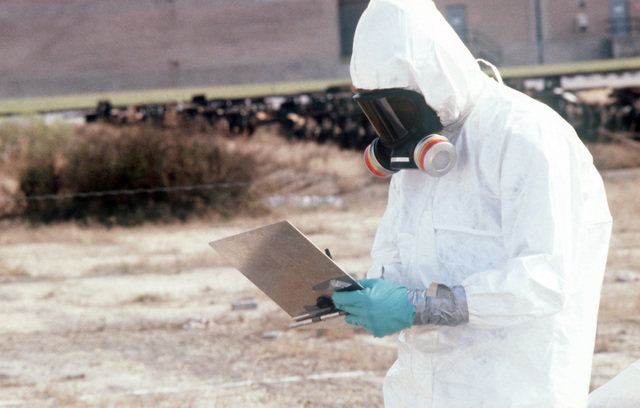 A decontamination technician charts the areas where soil samples have been collected from the Naval Construction Battalion Center dioxin elimination test site