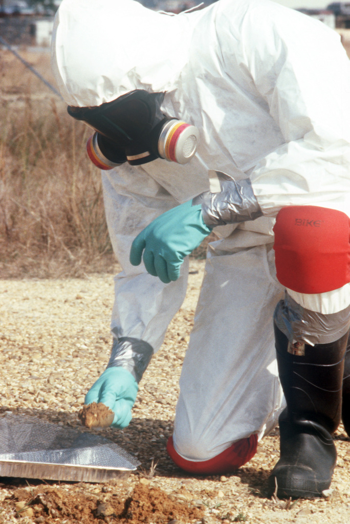 A decontamination technician wearing protective clothing collects soil samples at the Naval Construction Battalion Center dioxin elimination test site