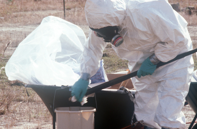A decontamination technician wearing protective clothing decontaminates his equipment before taking soil samples at the Naval Construction Battalion Center dioxin elimination test site