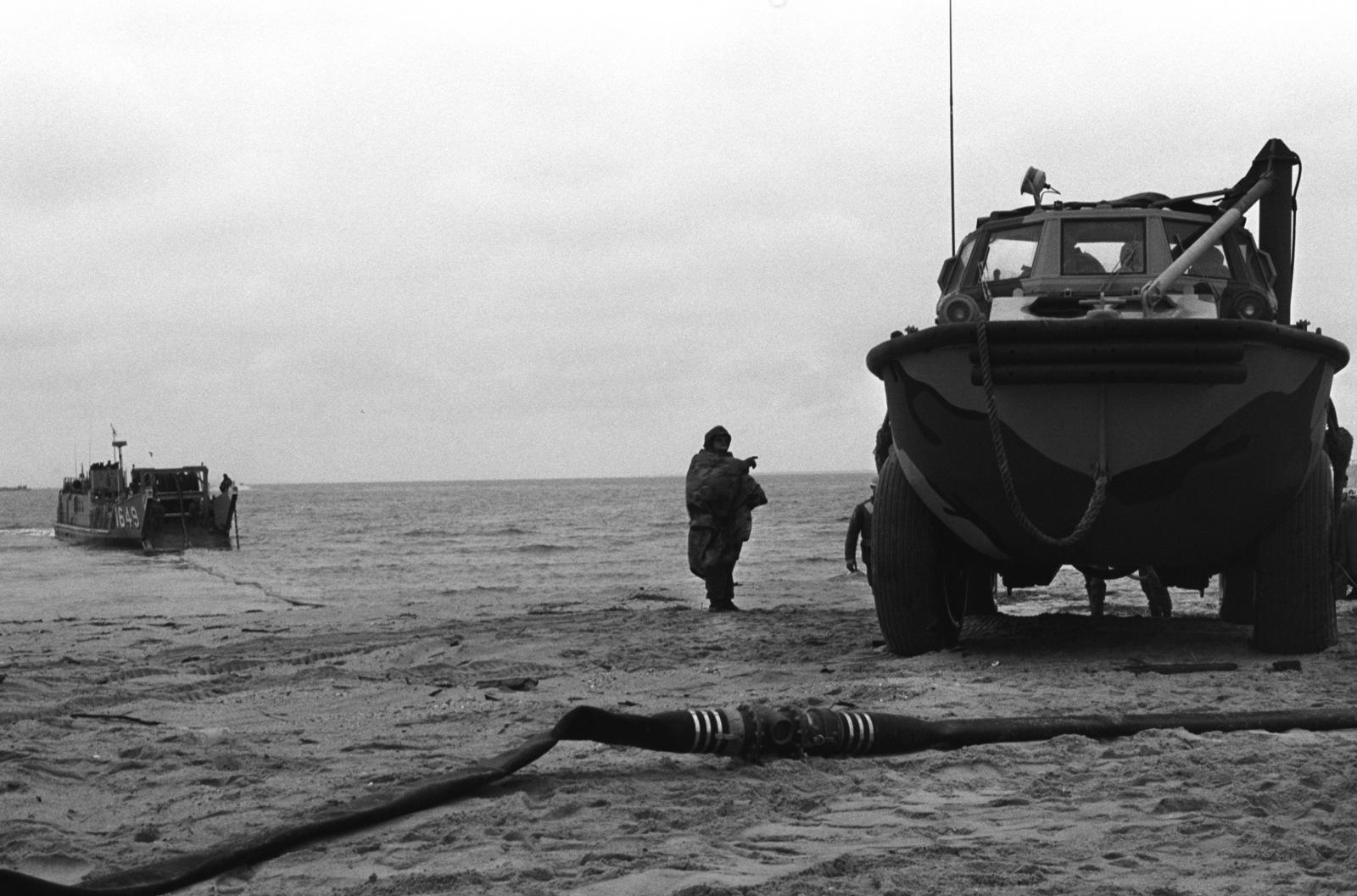 A US Marine guides a LARC 5 amphibious cargo carrier onto the beach