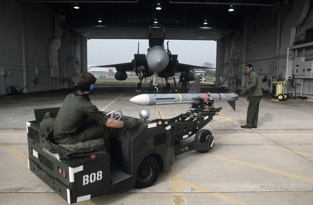 Technicians of the 48th Fighter Interceptor Squadron use a MJ-1 bomb loader to load an AIM-7 Sparrow missile to an F-15 Eagle aircraft during Exercise AMALGHAM CHIEF '87-1