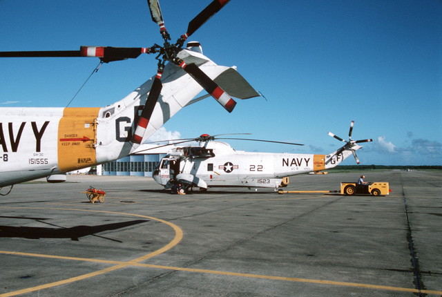 A ground crewman in an MD-3A tow tractor prepares to tow an SH-3G Sea King helicopter from Fleet Composite Squadron Eight (VC-8)