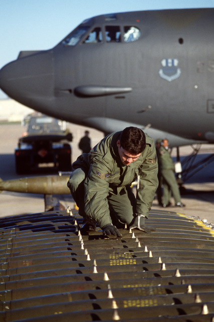 A member of the 2nd Munitions Maintenance Squadron inspects general purose bombs on a bomb rack before they are loaded on the wing of a B-52G Stratofortress aircraft during an operational readiness inspection by the Strategic Air Command Inspector General Team