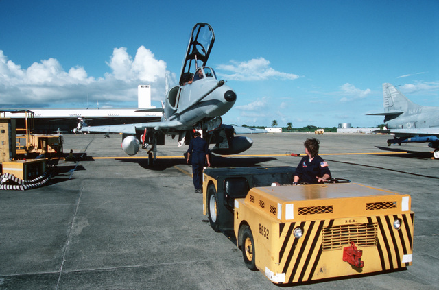 An A-4E Skyhawk aircraft from Fleet Composite Squadron Eight (VC-8) is towed by an MD-3A tow tractor