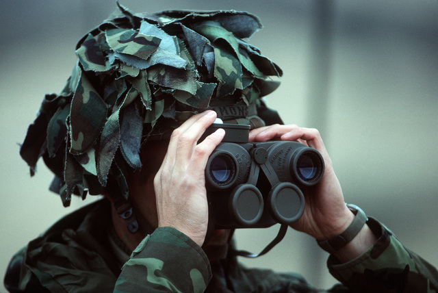 Colonel (COL) Simmons of the 7th Infantry Division uses field glasses to monitor progress during the joint US Army/Air Force Exercise CALFEX'86 (combined arms live fire exercise)