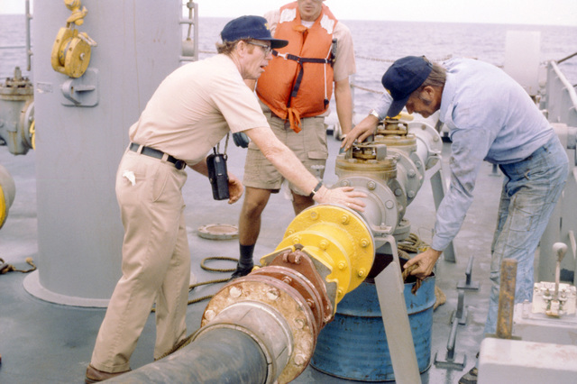 Crewmen aboard an oiler disconnects a fuel hose during an emergency breakaway drill with the fleet oiler USNS HASSAYAMPA (T-AO 145). The ships are participating in an underway replenishment operation