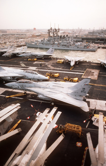 F-14A Tomcat aircraft and deck equipment cover the flight deck of the nuclear-powered aircraft carrier USS NIMITZ (CVN 68) as the ship prepares to depart Norfolk for its new home port in Bangor, Washington