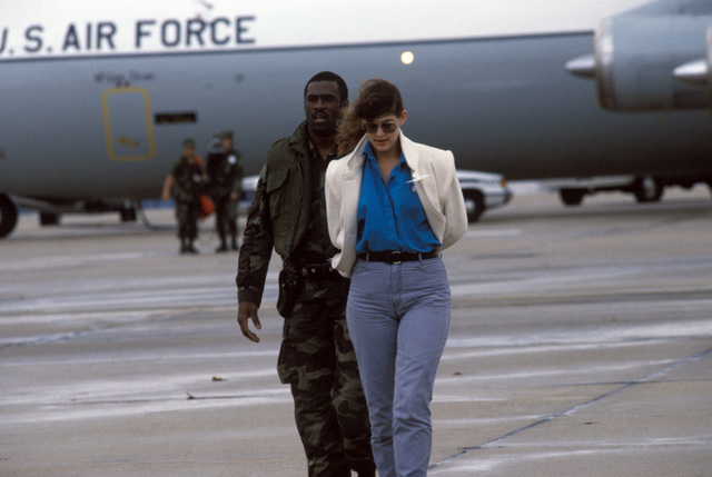 A member of the 438th Security Police Squadron escorts a member of the news media to safety after she strayed too close to a hijacked C-141B Starlifter aircraft during a simulated hijack exercise