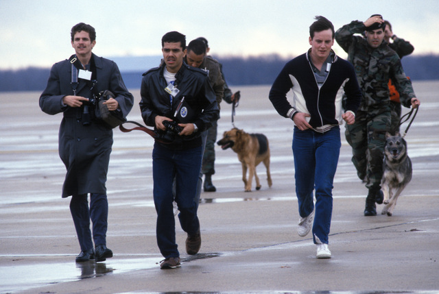 Members of the 438th Security Police Squadron escort members of the news media to safety after she strayed too close to a hijacked C-141B Starlifter aircraft during a simulated hijack exercise