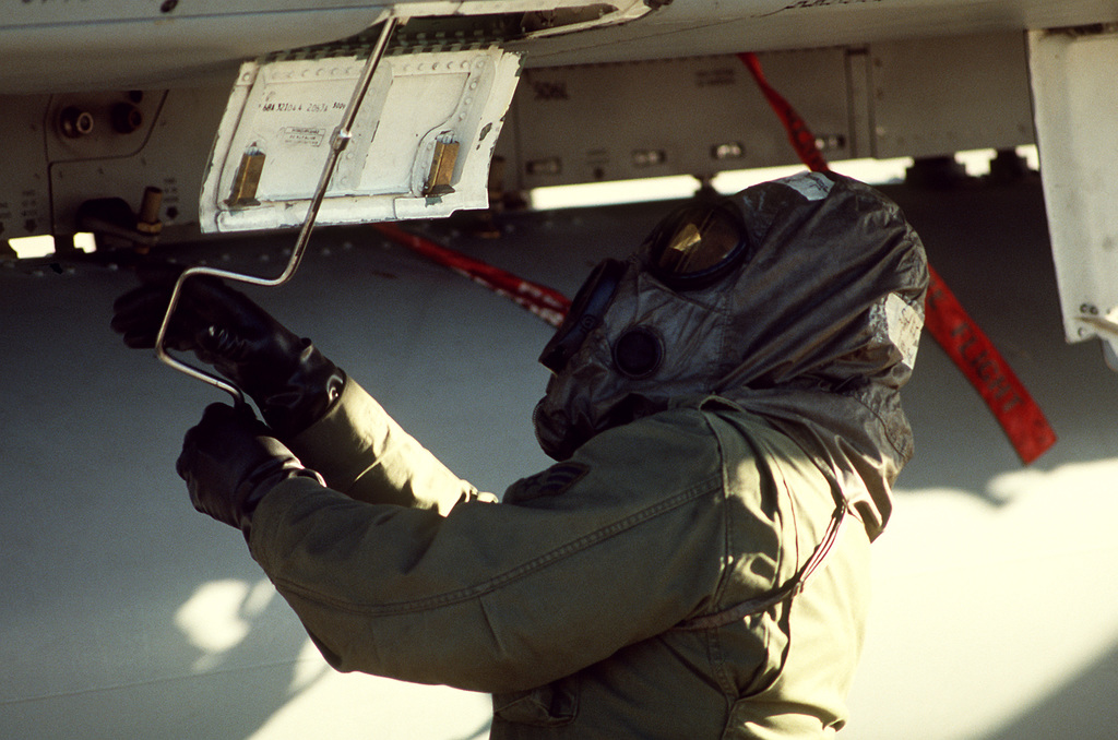 A ground crewman services a 33rd Tactical Fighter Wing aircraft during Nomad Thrust, a chemical warfare exercise designed to test the wing's readiness in case of enemy attack