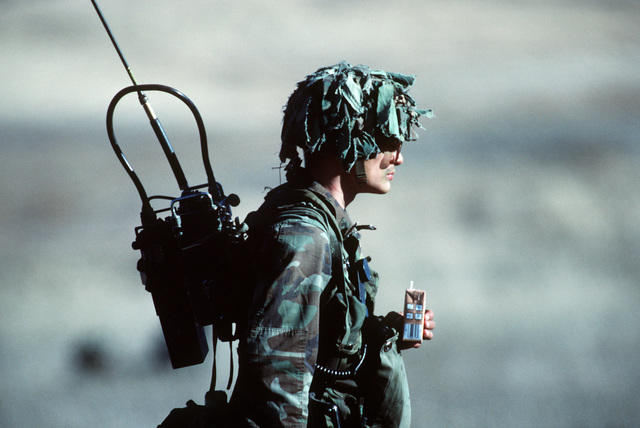 A radio operator of the 7th Infantry Division, armed with an M16A1 rifle, participates in the joint US Army/Air Force Exercise CALFEX'86 (combined arms live fire exercise)