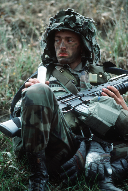 A Soldier of the 7th Infantry Division takes a break during the joint US Army/Air Force Exercise CALFEX'86 (combined arms live fire exercise).  His M16A1 rifle is equipped with an M203 40 mm grenade launcher