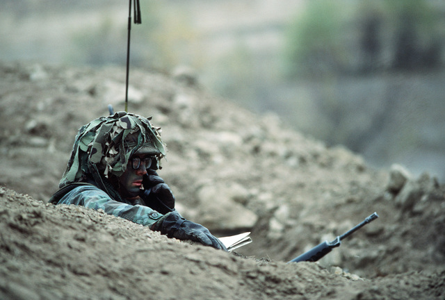 A Soldier of the 7th Infantry Division uses a field radio during the joint US Army/Air Force Exercise CALFEX'86 (combined arms live fire exercise)