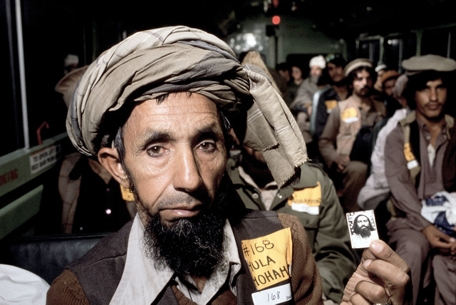 A wounded Afghan freedom fighter displays a photograph of his comrade while being bused to the Wiesbaden Regional Medical Center for an overnight layover while en route from Pakistan to the United States for treatment