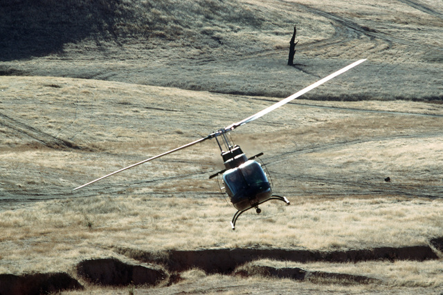 An OH-58 Kiowa helicopter from Company B, 307th Attack Helicopter Battalion, conducts a scouting mission during the joint US Army/Air Force Exercise CALFEX'86 (combined arms live fire exercise)