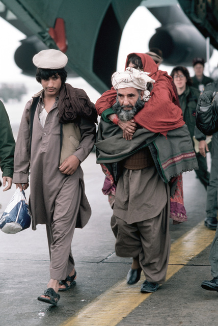 Wounded Afghan freedom fighters disembark from a C-141B Starlifter aircraft.  The freedom fighters are being transported to the Wiesbaden Regional Medical Center for an overnight layover while en route from Pakistan to the United States for treatment