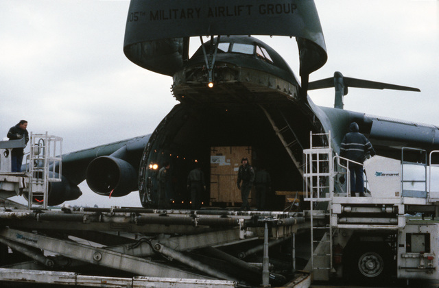 Industrial plant equipment is unloaded from a C-5A Galaxy aircraft.  The machinery will be used at an Aviation Classification Repair Activity Depot (AVCRAD) to repair military helicopters