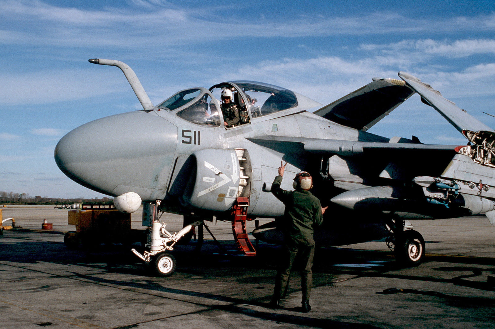 A ground crewman signals to the pilot of an A-6E Intruder aircraft from Attack Squadron 35 (VA-35) prior to a flight.  The aircraft is equipped with a Target Recognition and Attack Multisensor (TRAM) pod on the lower portion of its nose and carries Mark 76 Mod 5 practice bombs on its outboard wing pylon