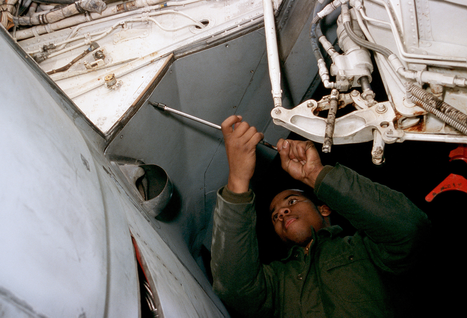 A mechanic tightens a panel near the open landing gear of an A-6E Intruder aircraft from Attack Squadron 35 (VA-35) during pre-deployment maintenance.  In less than three weeks VA-35 and the other squadrons of Carrier Air Wing 8 (CVW-8) will begin a deployment to the Western Pacific aboard the nuclear-powered aircraft carrier USS NIMITZ (CVN 68)
