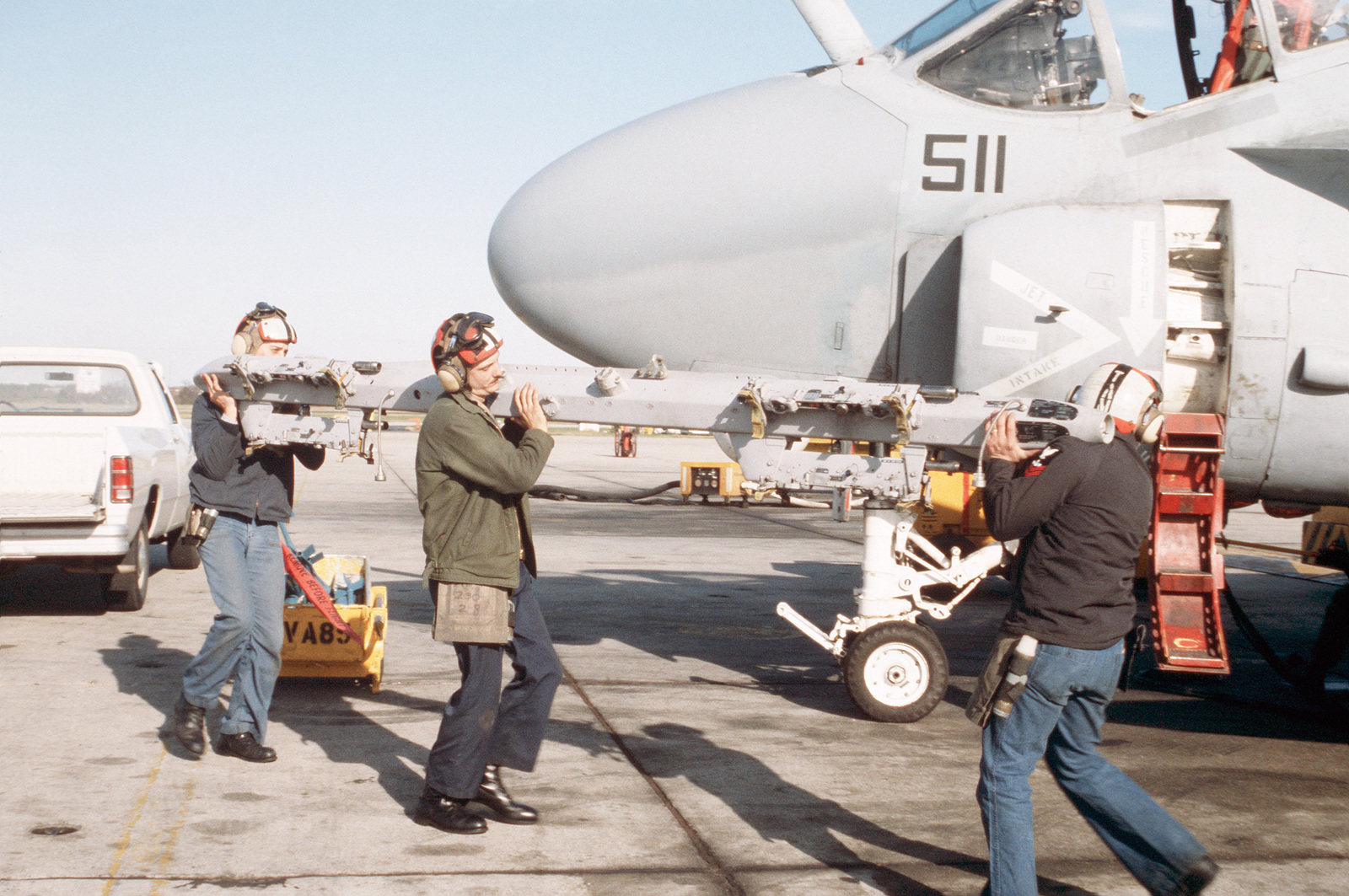 Ground crewmen from Attack Squadron 35 (VA-35) carry a bomb rack to the left wing of one of the Squadron's A-6E Intruder aircraft prior to mounting practice ordnance