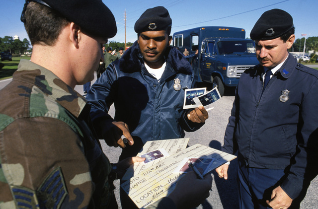 Staff Sergeant (SSGT) Carder, left, Sergeant (SGT) Jerome Neal and Technical Sergeant (TSGT) William Harwood, right, all members of the 834th Security Police Squadron, examine photos of demonstrators who were arrested for trespassing at Hurlburt Field.  Approximately 300 people are gathered outside the base to protest the training of Nicaraguan Contra rebels