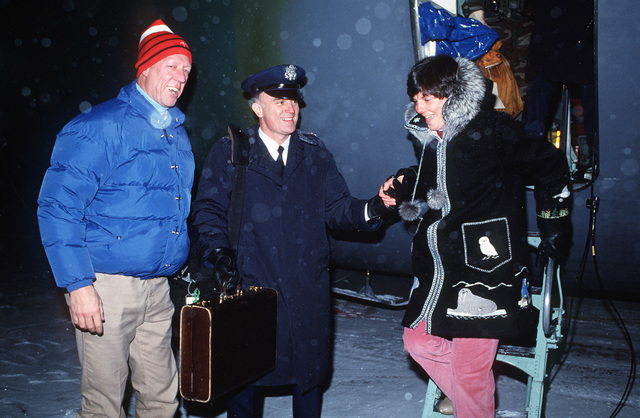 "Television celebrity David Hartman stands by on the flight line as Colonel (COL) Mannen O. Clements, base commander, helps Mrs. Clements step down from a C-141B Starlifter aircraft after greeting Hartman.  Hartman is at Goose Bay during a stopover en route to Thule Air Base, Greenland, where he and his crew will film a segment for his program""Good Morning America."""