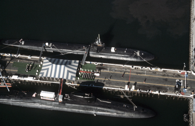 An elevated view of the nuclear-powered attack submarine USS BALTIMORE (SSN 704) and the nuclear-powered fleet ballistic missile submarine USS NATHANIEL GREENE (SSBN 636), foreground, moored at Pier No. 22 of the naval station. The NATHANIEL GREEN is being decommissioned