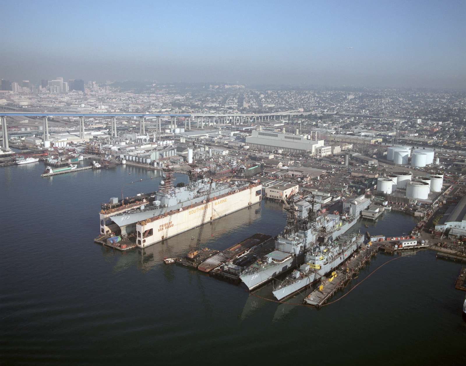 The US Navy (USN) Spruance Class Destroyer USS JOHN YOUNG (DD 973) in dry dock at the Southwest Marine Inc shipyard at San Diego, California (CA). To the portside of the JOHN YOUNG are the USS FIFE (DD 991) and USN Escort Destroyer USS BROOKE (DEG-1/FFG-1). In the background are the Coronado Bridge and the city of San Diego