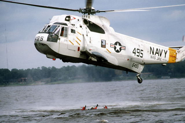 An SH-3D Sea King helicopter hovers over a Sea and Air Rescue (SAR) aircrewman with a student from aviation cadet training group D-West