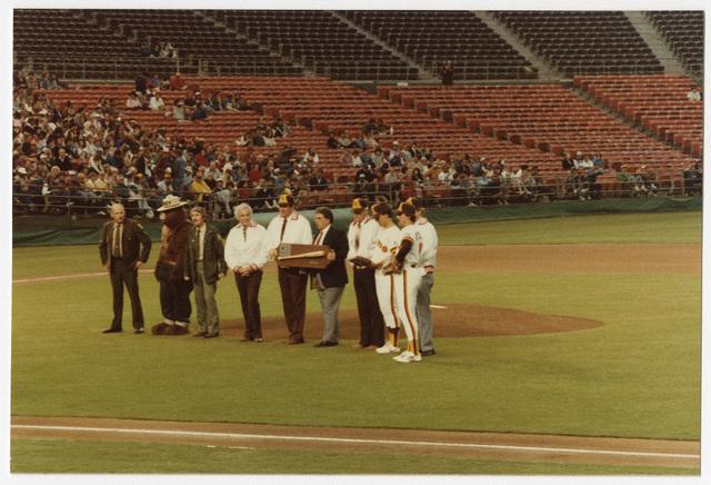 Group of U.S. Forest Service Rangers and Padres Organization Members on Field at Jack Murphy Stadium with Smokey Bear during Smokey Bear Baseball Card Night