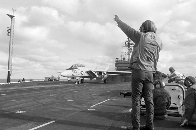 A catapult and arresting gear officer prepares to signal for the launch of an F-14A Tomcat aircraft during flight operations aboard the aircraft carrier USS CONSTELLATION (CV 64)