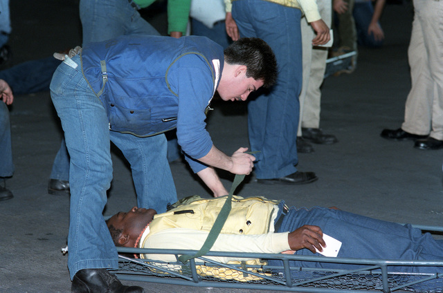 A crew member straps a simulated casualty onto a Stokes litter during a general quarters drill aboard the nuclear-powered aircraft carrier USS THEODORE ROOSEVELT (CVN 71)
