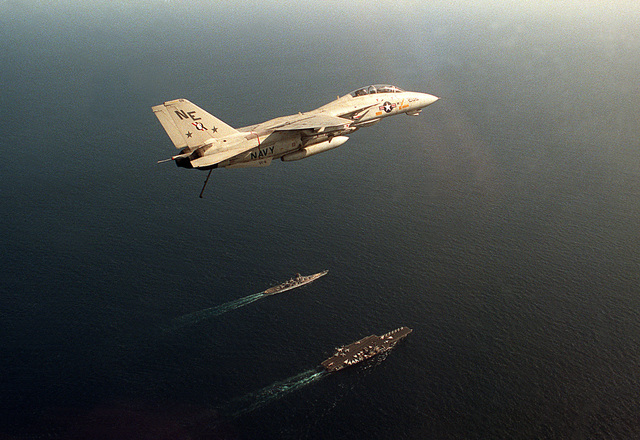 A Fighter Squadron 2 (VF-2) F-14A Tomcat aircraft passes over the aircraft carrier USS RANGER (CV-61) and an Iowa-class battleship during a flight off of the Ranger