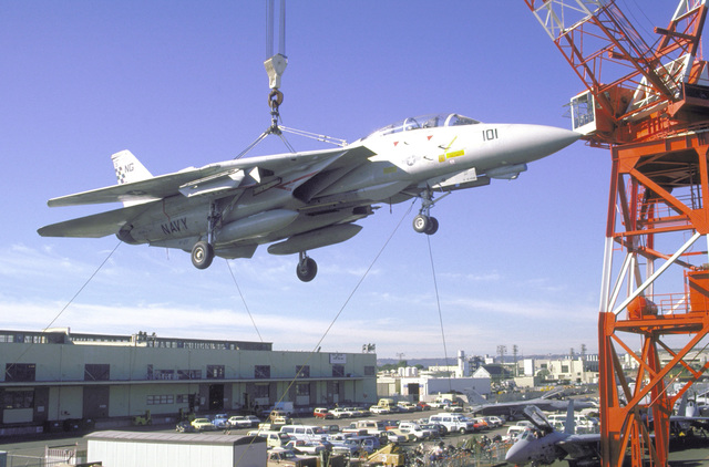 A Fighter Squadron 211 (VF-211) F-14A Tomcat aircraft is hoisted by crane aboard the aircraft carrier USS KITTYHAWK (CV-63)