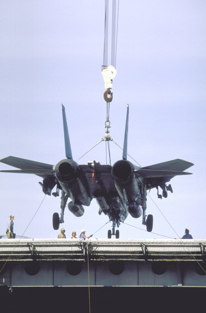 A Fighter Squadron 211 (VF-211) F-14A Tomcat aircraft is lowered by crane onto the deck of the aircraft carrier USS KITTYHAWK (CV-63)