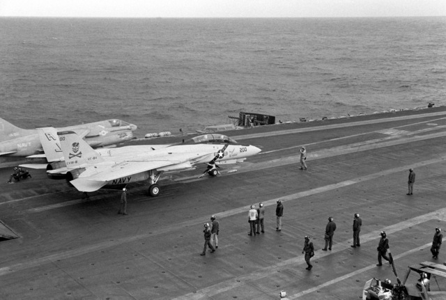 A Fighter Squadron 84 (VF-84) F-14A Tomcat aircraft waits on the No. 3 waist catapult as an Attack Squadron 82 (VA-82) A-7E Corsair II aircraft is launched from the No. 4 waist catapult aboard the nuclear-powered aircraft carrier USS NIMITZ (CVN 68)
