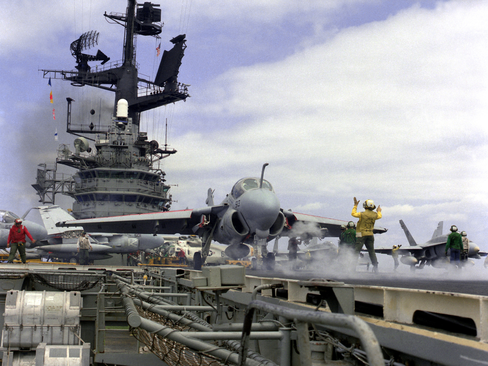 A flight deck crew member signals to the pilot of an A-6E Intruder aircraft as the plane is readied for launch from the aircraft carrier USS CORAL SEA (CV-43)