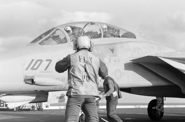 A flight deck crewman makes final pre-launch checks on a Naval Air Reserve Fighter Squadron 301 (VF-301) F-14A Tomcat aircraft during flight operations aboard the aircraft carrier USS CONSTELLATION (CV 64)