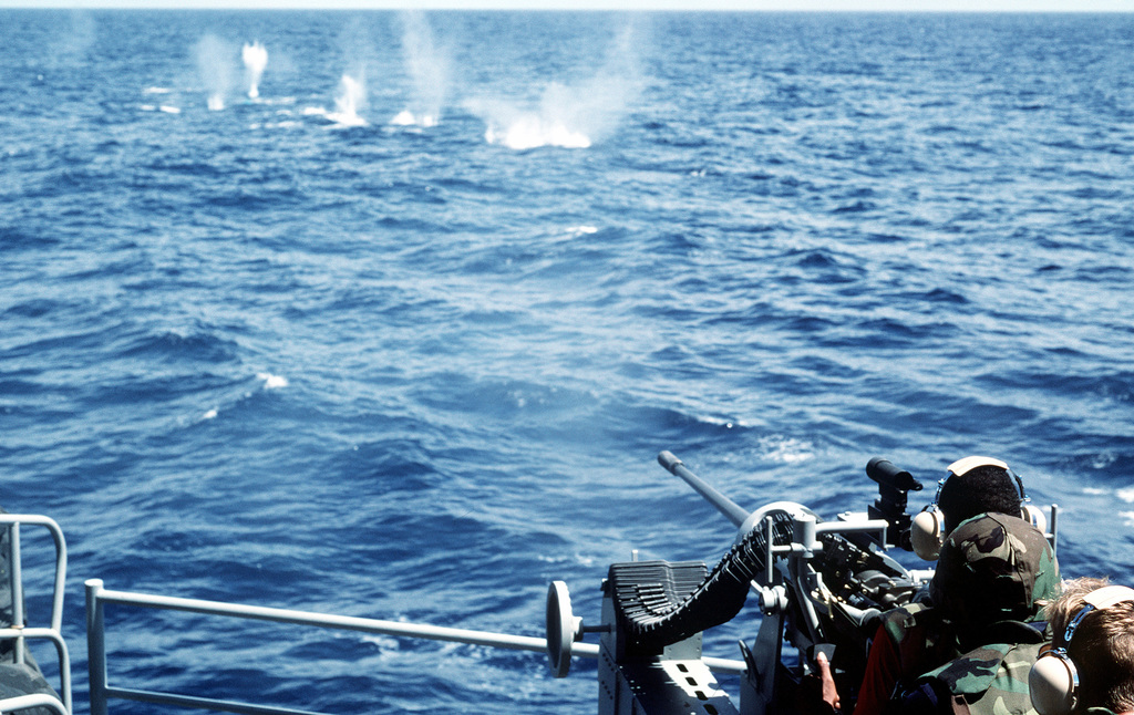 A member of the Marine detachment aboard the battleship USS MISSOURI (BB-63) strafes the water with bullets as he fires a Mark 38 25mm gun system during exercise RIMPAC '87