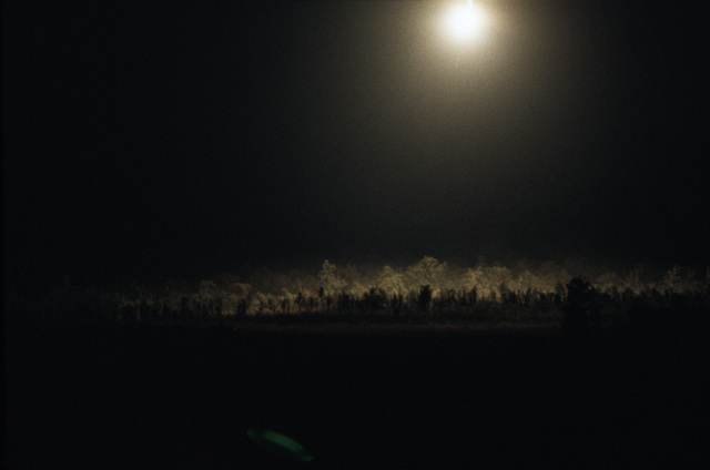 "A nighttime view of the firing range illuminated by a magnesium flare during a live fire Exercise""MAD MOMENT."""