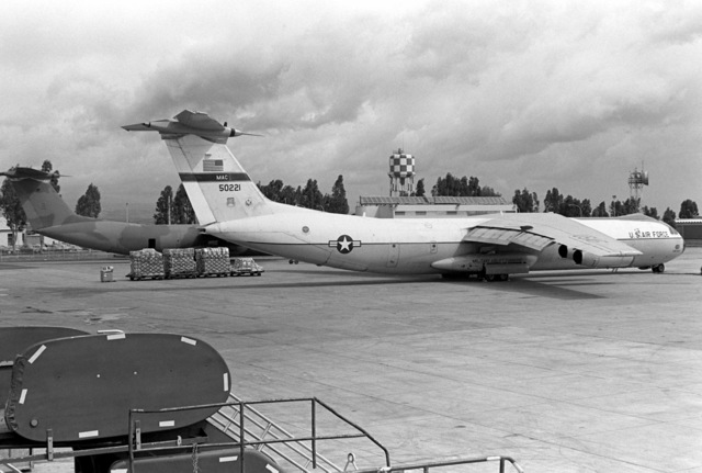 A pair of US Air Force C-141B Starlifter aircraft sit on the flight line during a stopover at the air station