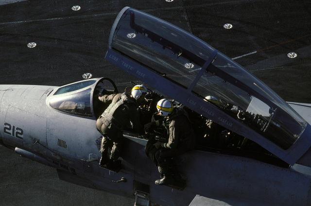 A pilot and the radar intercept officer climb out of the cockpit of an F-14A Tomcat aircraft during Naval Air Reserve carrier qualifications aboard the aircraft carrier USS CONSTELLATION (CV 64)