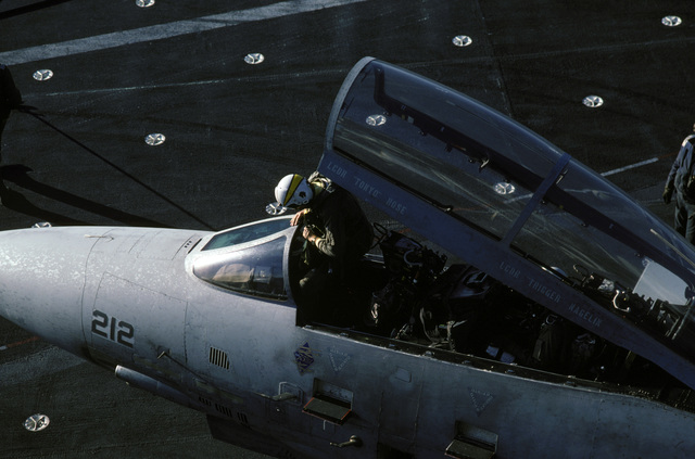 A pilot climbs out of the cockpit of an F-14A Tomcat aircraft during Naval Air Reserve carrier qualifications aboard the aircraft carrier USS CONSTELLATION (CV 64)
