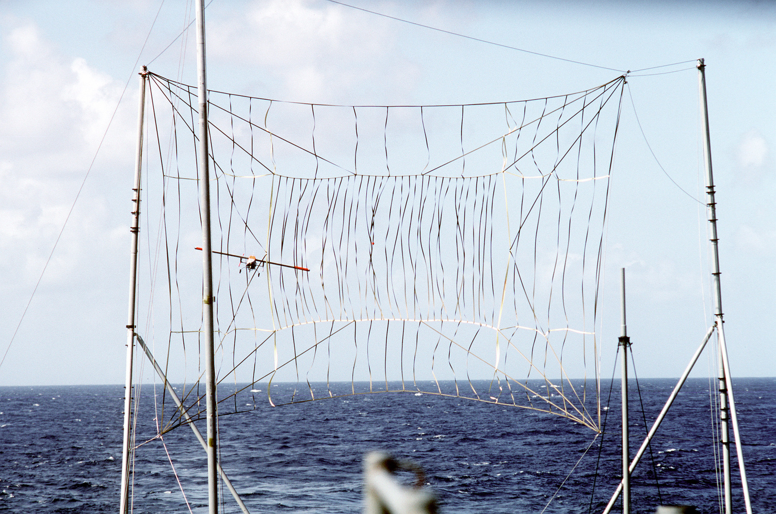 A Pioneer I remotely piloted vehicle (PV) approaches a recovery net erected on the stern of the battleship USS IOWA (BB-61). The RPV, which carries a stabilized television camera and a laser designator, is being tested aboard the IOWA as a basic gunfire support system with over-the-horizon targeting and reconnaissance capabilities. The system may be operated out to a range of 110 miles from the battleship surface group and has endurance of eight hours